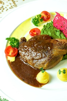 Close up view of roast duck leg with avocado sauce and mashed potatoes with cherry tomatoes