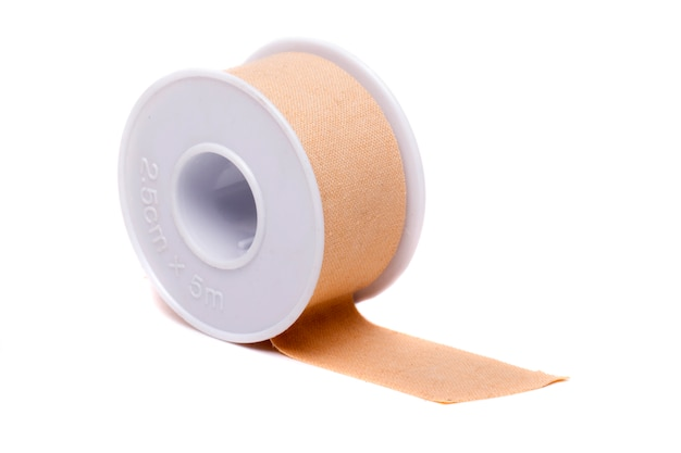 Close up view of a roll of masking tape isolated on a white background.