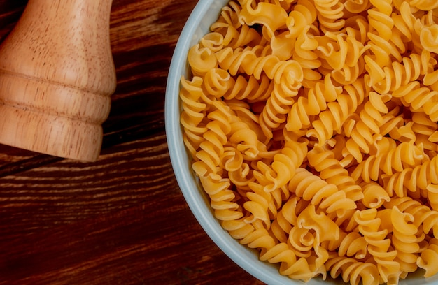 Close-up view of rotini pasta in bowl with salt on wooden table