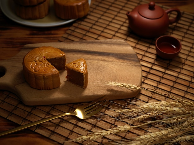 Close up view of rustic table setting in moon festival with moon cake and tea set on bamboo placemat in chinese restaurant