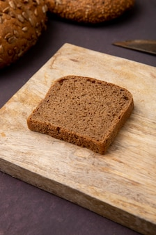 Close-up view of rye bread slice on wooden surface and maroon background