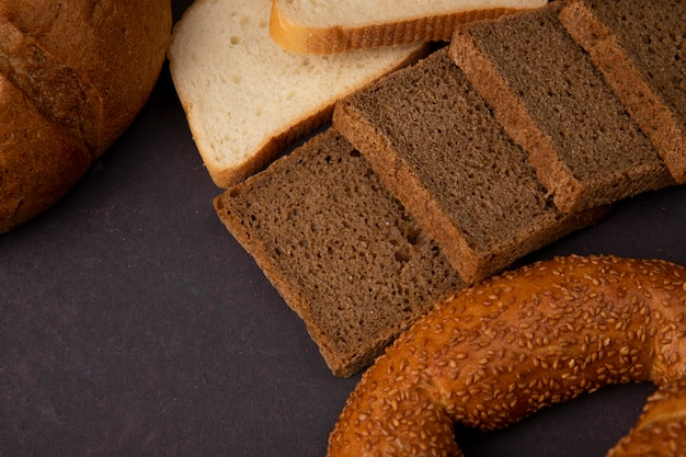 Close-up view of rye bread slices with white bread slices cob and bagel on maroon background with copy space