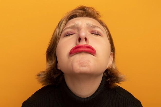 Vista ravvicinata della giovane ragazza bionda triste con gli occhi chiusi isolata sulla parete arancione