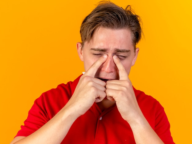 Close-up view of sad young handsome blonde ill man touching nose with closed eyes isolated on orange wall