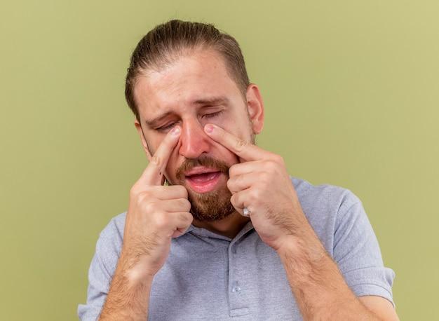 Vista ravvicinata di triste giovane bello slavo malato che tiene il tovagliolo che mette le dita sotto gli occhi con gli occhi chiusi isolati sulla parete verde oliva
