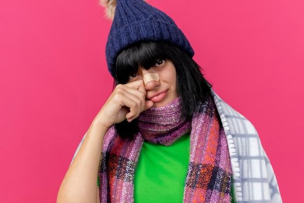 Vista ravvicinata di triste giovane donna malata che indossa cappello invernale e sciarpa avvolta in un plaid guardando la parte anteriore con intonaco sul naso che tocca il viso isolato sul muro rosa