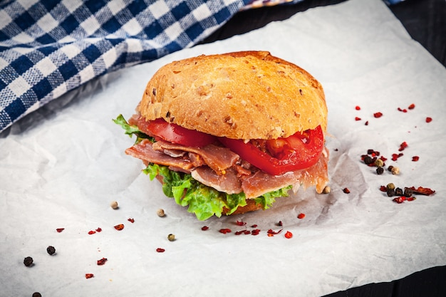 Close up view on sandwich with prosciutto, lettuce, tomato on white surface