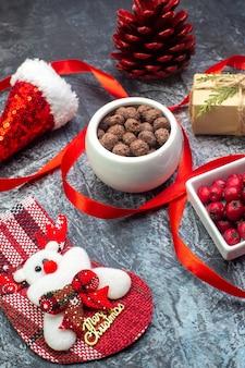 Vista ravvicinata del cappello di babbo natale e del regalo di cono di conifere rosso del calzino di cioccolato cornel del nuovo anno su superficie scura