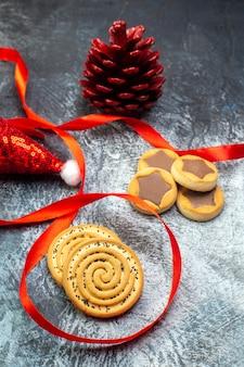Vista ravvicinata del cono di conifere rosso del cappello di babbo natale e di vari biscotti sulla superficie scura