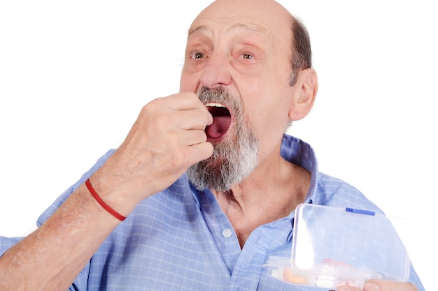 Close up view of senior man taking pill