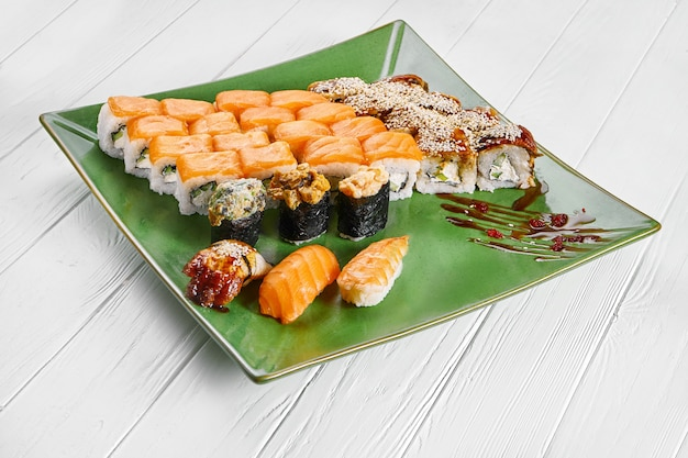 Close up view on set of assorted roll and sushi on green plate isolated on white wooden background. sushi with salmon, eel. japanese sushi food