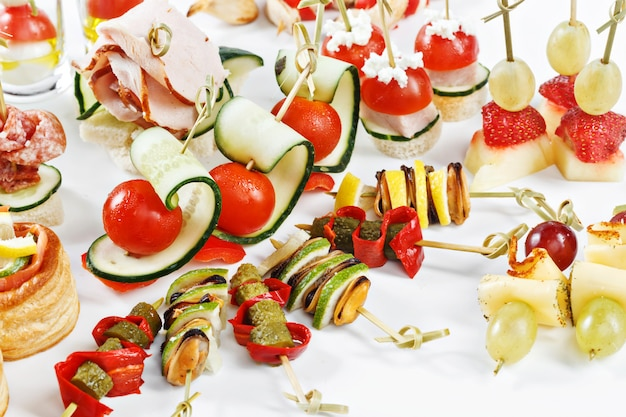 Close-up view set of canapes with vegetables, salami, seafood, meat and decoration on white plate