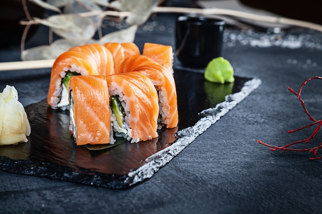 Close up view on set of sushi roll. philadelhia roll with salmon and cheese served on black stone on dark background. japanese cuisine. copy space. served sushi for menu. healthy food, seafood