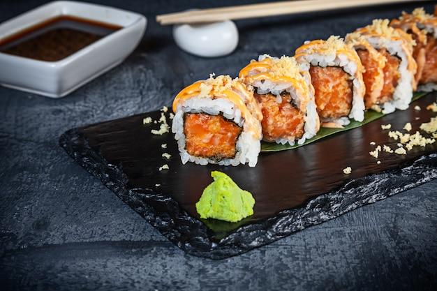 Close up view on set of sushi roll. spicy roll with salmon and caviar served on black stone on dark background. japanese cuisine. copy space. served sushi for menu. healthy food, seafood