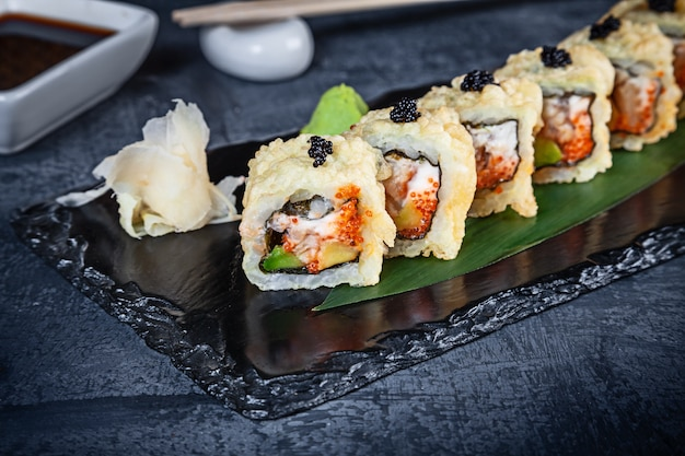 Close up view on set of sushi roll. warm roll with eel and caviar served on black stone on dark background. japanese cuisine. copy space. served sushi for menu. healthy food, seafood