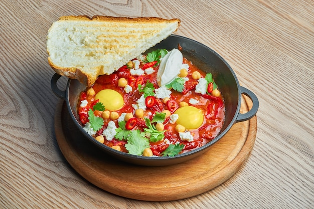 Close up view on shakshuka with hot chili pepper in tomato juice with the addition of chickpea, cheese and bell pepper. traditional israeli cuisine