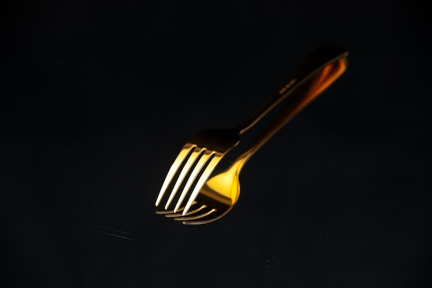Close up view of shiny golden fork put upside down on black blurred background with free space