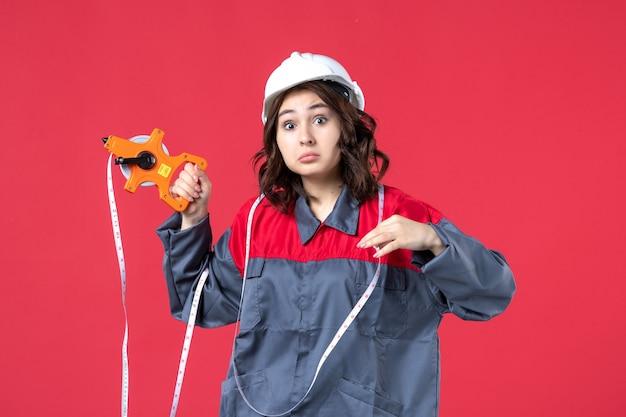 Vista ravvicinata di scioccato architetto femminile emotivo in uniforme che indossa elmetto con nastro di misurazione sulla parete rossa