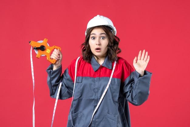Vista ravvicinata di scioccato architetto femminile in uniforme che indossa elmetto con nastro di misurazione sulla parete rossa