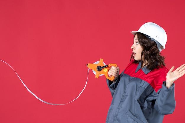 Chiuda sulla vista dell'architetto femminile scioccato in uniforme con nastro di misurazione di apertura del cappello duro sulla parete rossa isolata
