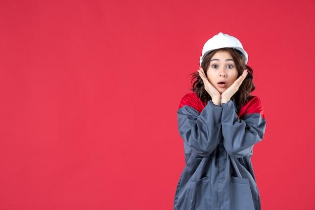 Vista ravvicinata del costruttore femminile scioccato in uniforme con elmetto e concentrato su qualcosa sulla parete rossa isolata