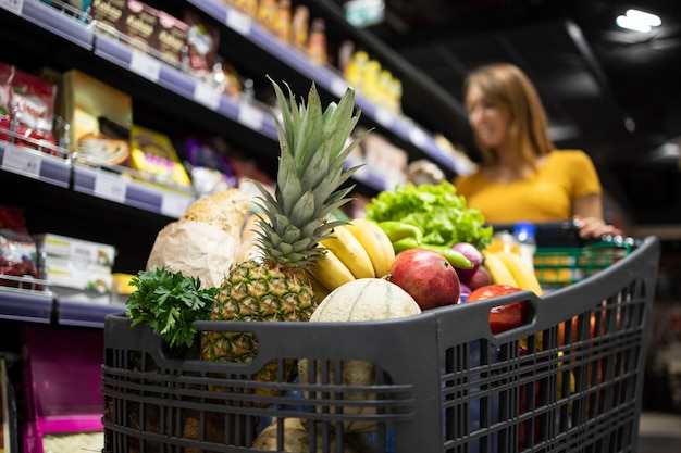 Close up view of shopping cart overloaded with food while in background female person choosing products