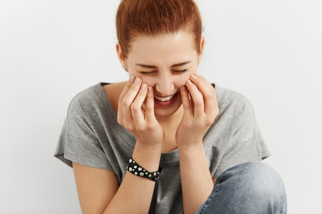Close up view of shy caucasian college student touching her cheeks with both hands looking happy and carefree, having clean skin and manicured fingers, laughing at funny joke. youth and happiness