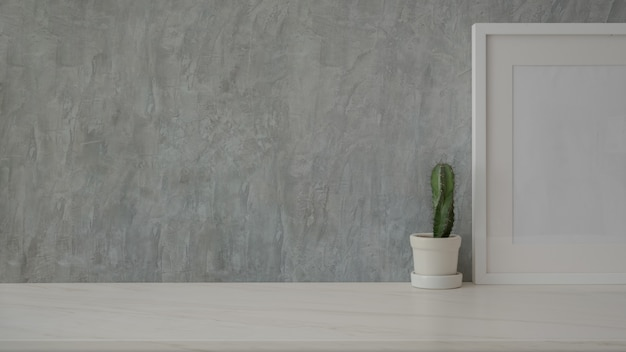 Close up view of simple copy space with mock-up frame and cactus pot on marble table