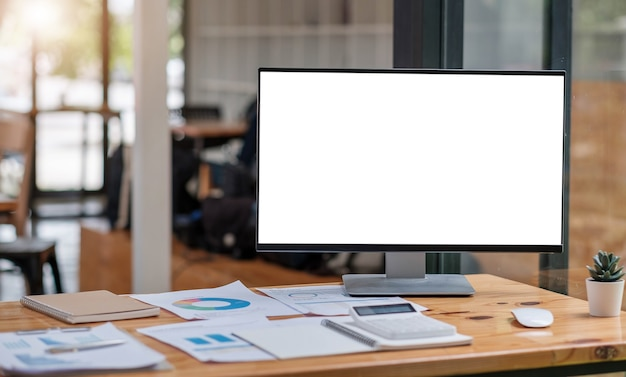 Close up view of simple workspace with open blank screen laptop, frame and notebook on white table with blurred office room background