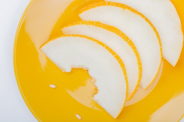 Close-up view of sliced melon in plate on white background