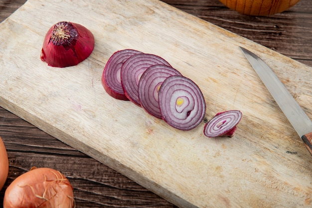 Close-up view of sliced red onion with knife on wooden surface and wooden background