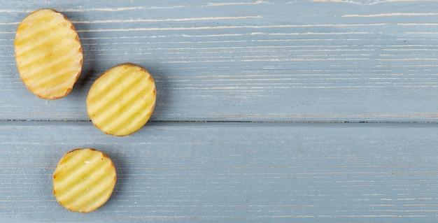 Chiuda sulla vista delle fette affettate e increspate della patata dalla parte di sinistra e del fondo di legno con lo spazio della copia