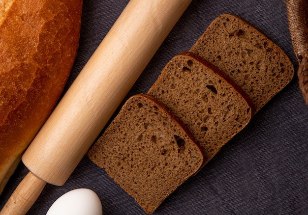 Close-up view of sliced rye bread and rolling pin with egg on maroon background