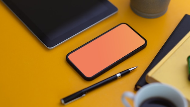 Close up view of smartphone with mock up screen on yellow table with stationery and coffee cup