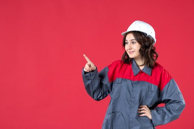Chiuda sulla vista del costruttore femminile sorridente in uniforme con il cappello duro e che indica qualcosa sulla parete rossa isolata