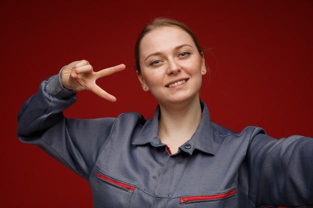 Vista ravvicinata di sorridente giovane bionda ingegnere femminile che indossa l'uniforme allungando la mano verso la telecamera che mostra il simbolo del segno di v vicino all'occhio