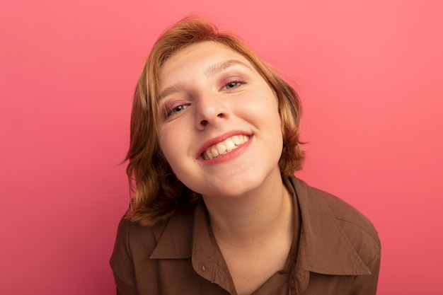 Close-up view of smiling young blonde girl looking  isolated on pink wall