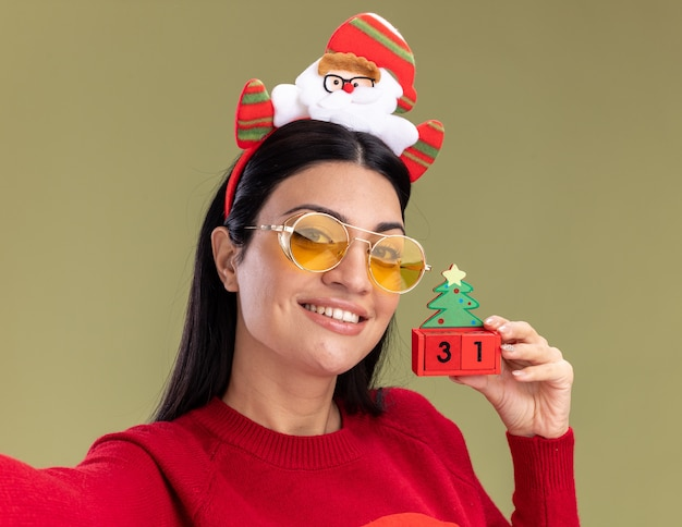 Close-up view of smiling young caucasian girl wearing santa claus headband and sweater with glasses holding christmas tree toy with date looking at camera isolated on olive green background