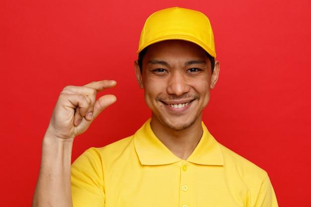 근접 촬영보기 웃는 젊은 배달 남자 유니폼과 모자 소량 제스처를 하 고