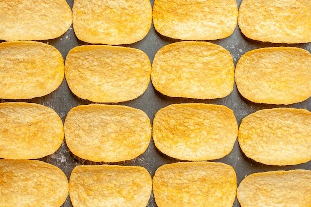 Vista ravvicinata di uno spuntino party per gli amici con deliziose patatine sul tavolo grigio
