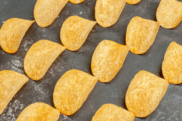Close up view of snack party for friends with tasty potato chips on gray table