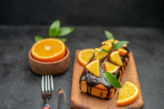 Vista ravvicinata di torte morbide a bordo e arance tagliate con foglie sul tavolo scuro