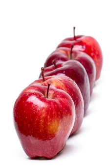 Close up view of some red apples in a row isolated on a white background.
