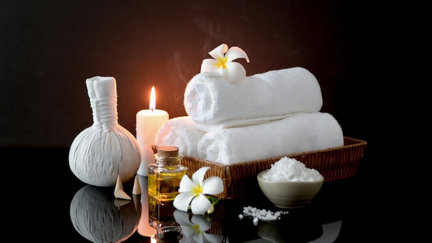 Close up view of spa treatment accessories with white towel, candle and aroma oil