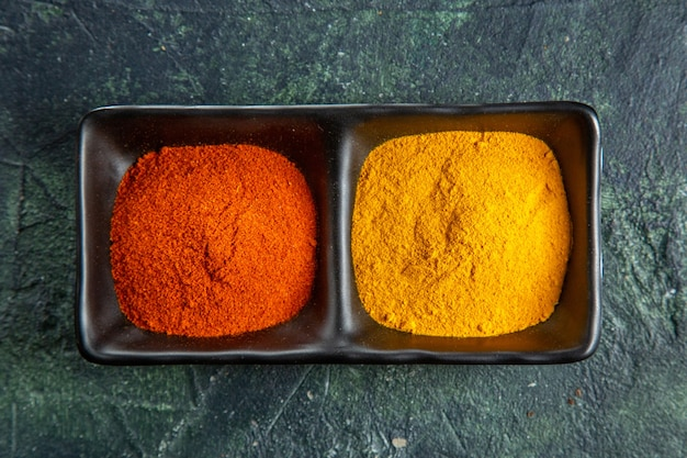 Close up view of spice bowls fulfilled with red pepper and yellow ginger on mix colors surface with free space