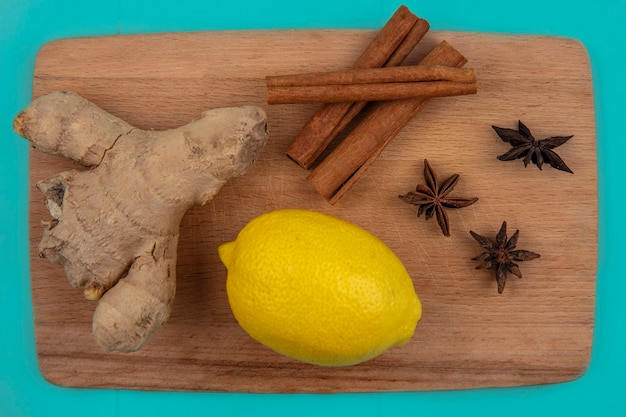 Close-up view of spices as ginger and cinnamon with lemon on cutting board on blue background