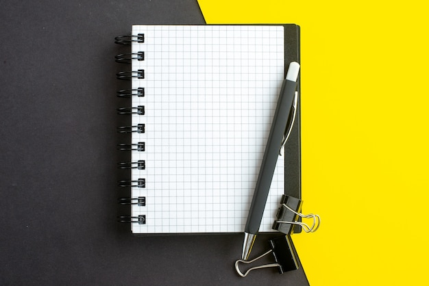 Close up view of spiral notebook on book and pens on black yellow background with free space
