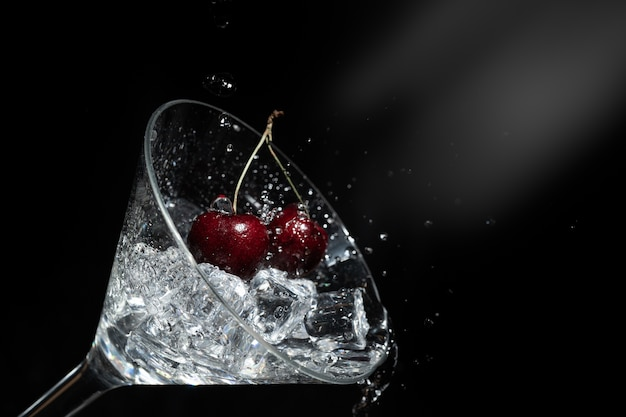 Close up view of splash water with falling cherry in a martini glass among ice in black ba