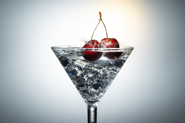 Close up view of splash water with falling cherry in a martini glass.
