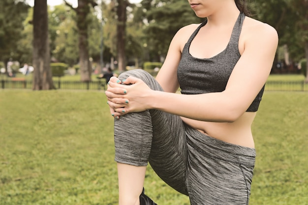 Close up view of sport woman streching legs
